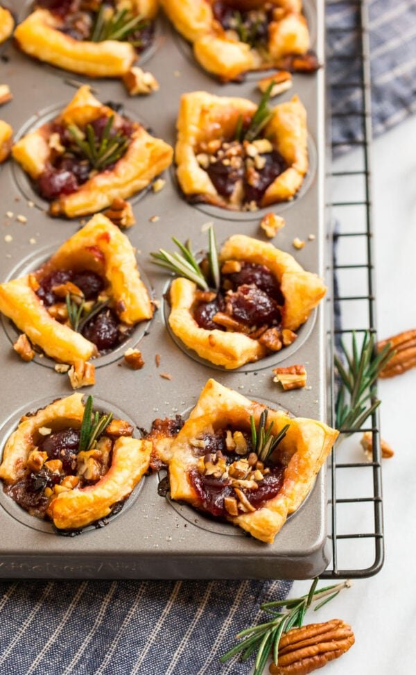 Delicious cranberry and puff pastry appetizers in a mini muffin tin with fresh rosemary