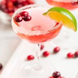 Two glasses of cranberry St.Germain cocktails with lime wedges