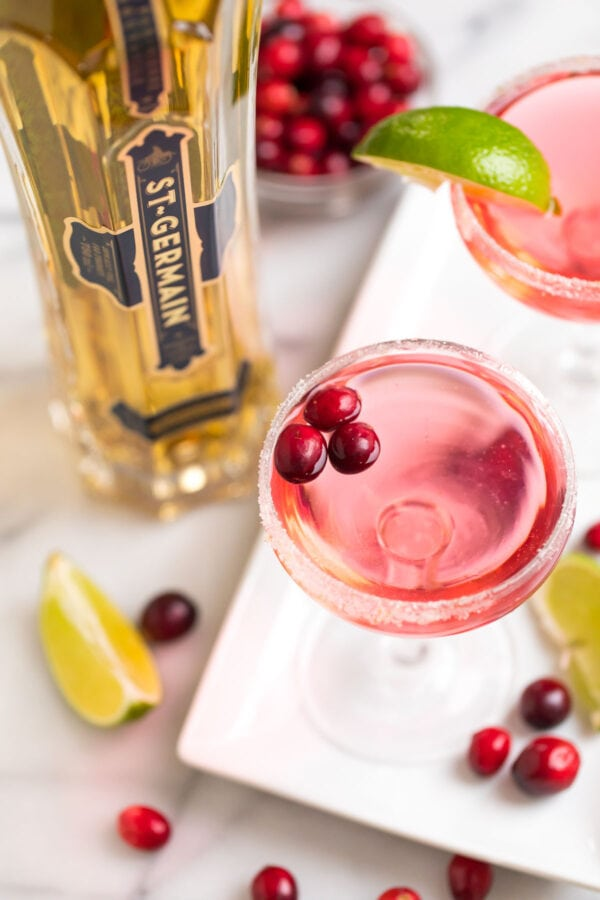 Delicious and festive cranberry St. Germain cocktail served in glasses with lime
