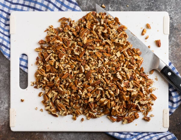 A cutting board with chopped pecans