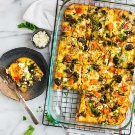 A pan with a vegetarian breakfast casserole sliced for a crowd with a slice of the casserole on a plate