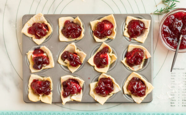 Puff pastry squares, Brie cheese, and cranberry sauce in a mini muffin tin