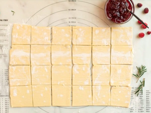 A sheet of puff pastry dough cut into squares for making a holiday appetizer