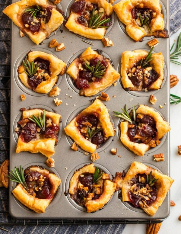Baked cranberry and Brie puff pastry appetizers in a mini muffin tin