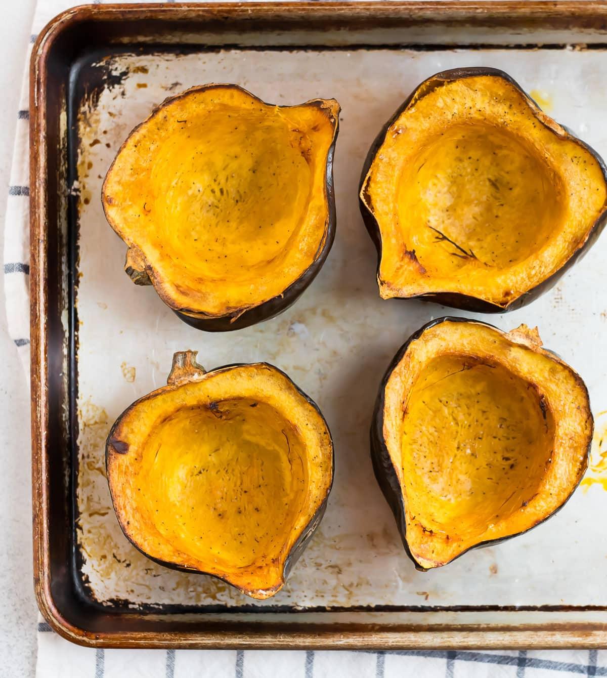 roasted acorn squash halves on a baking sheet
