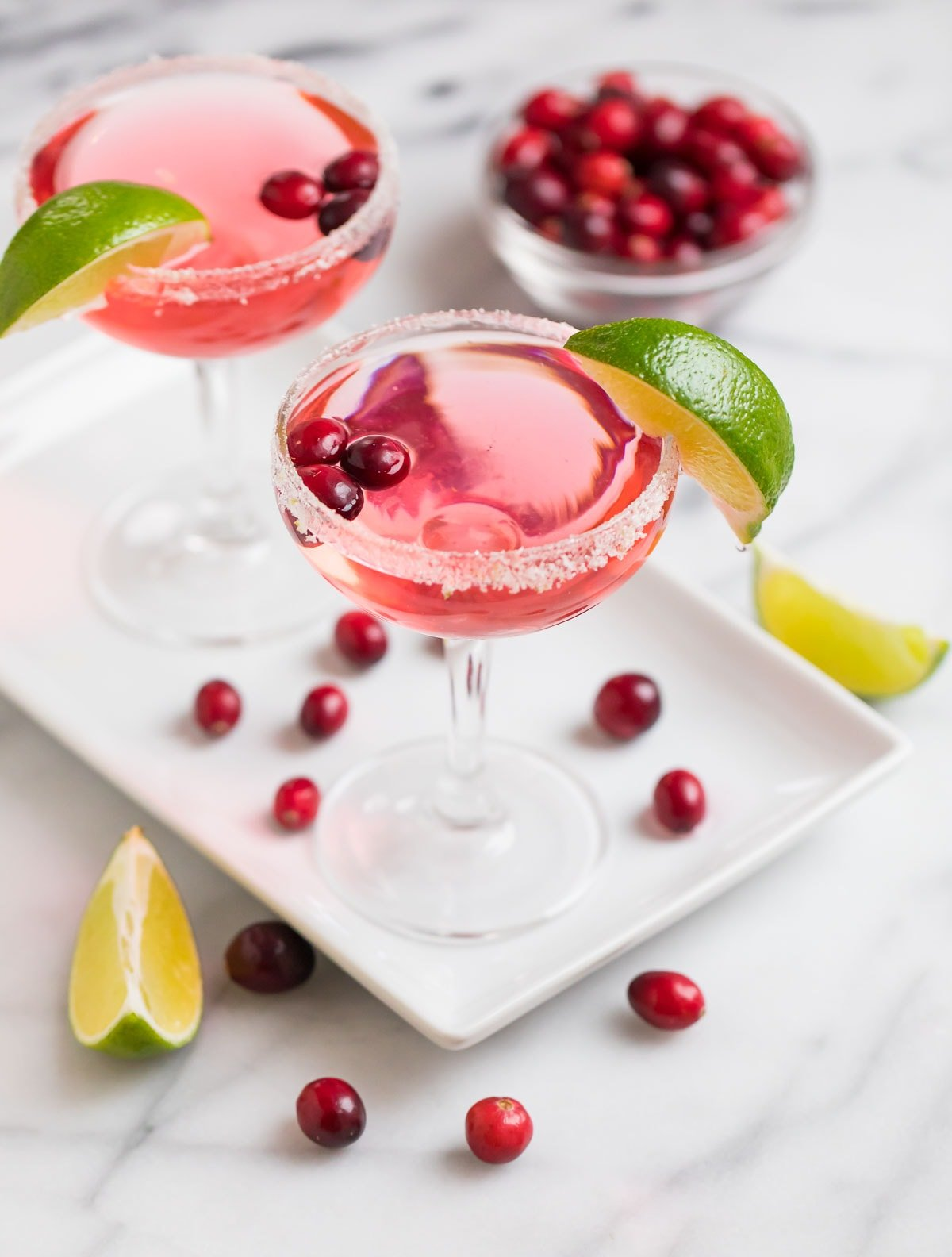 Delicious cranberry St. Germain cocktails on a plate with lime slices and cranberries