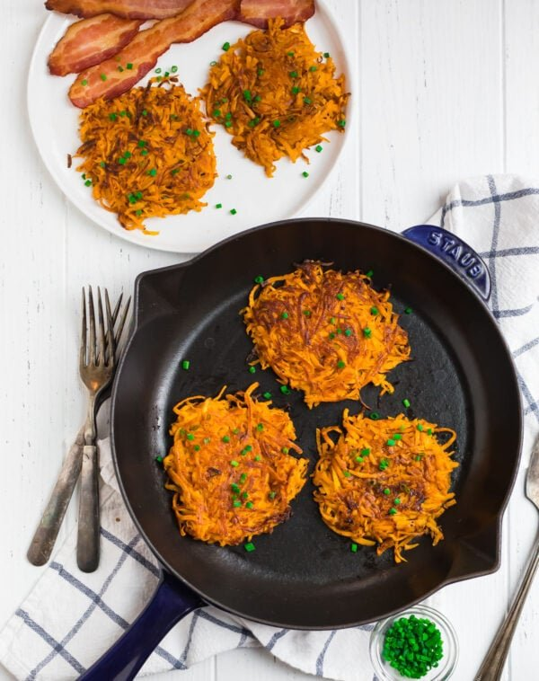 Easy hash browns made with sweet potatoes in a skillet and served on a plate with bacon
