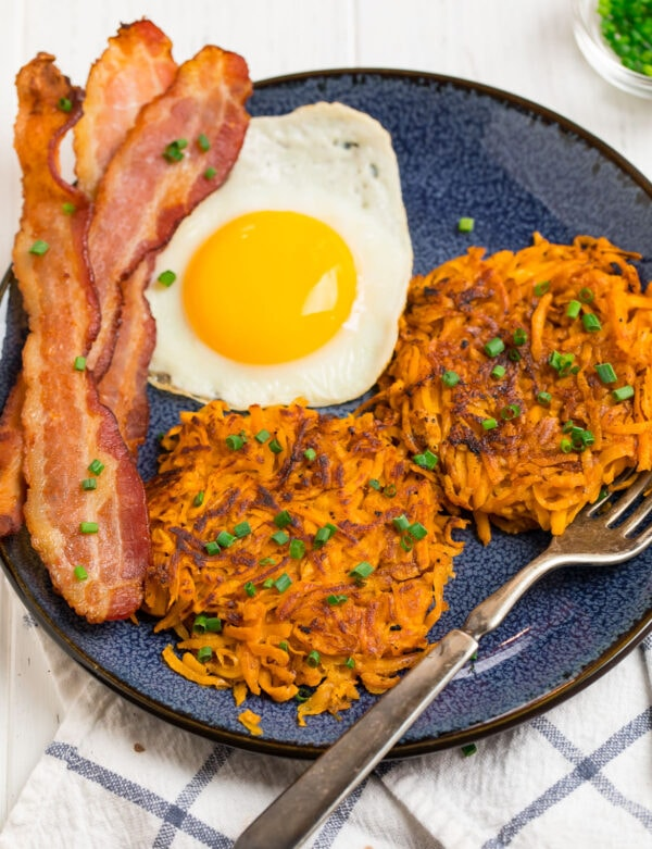 Sweet potato hash browns, eggs, and bacon served on a plate for an easy breakfast