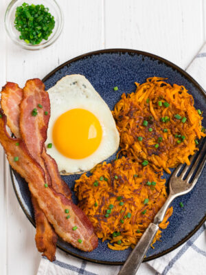 A blue plate with sweet potato hash browns, eggs, and bacon.