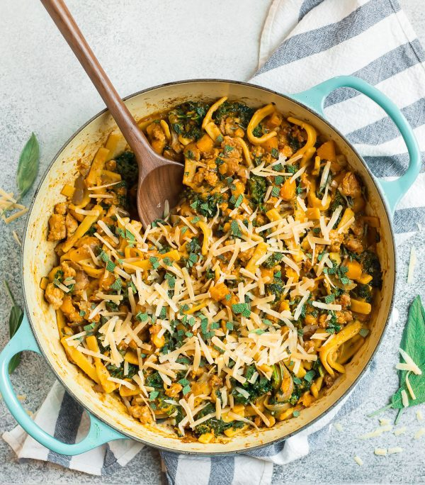 A large pot filled with butternut squash pasta, cheese, and herbs