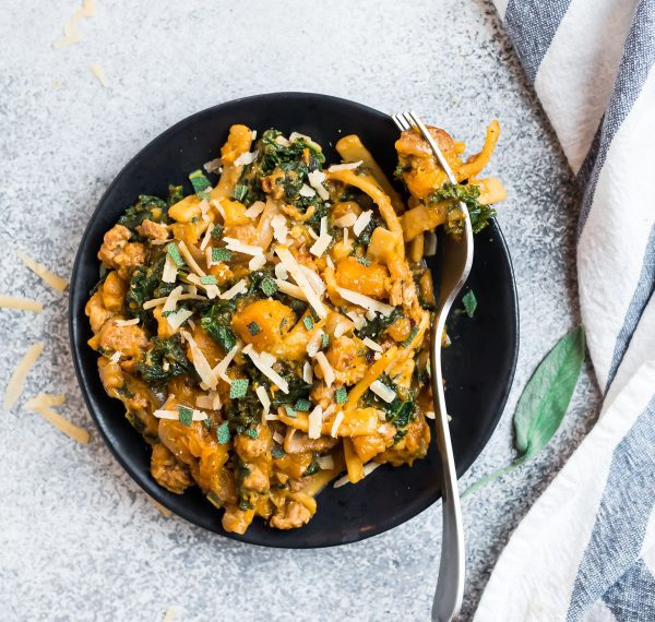 A black plate filled with butternut squash pasta