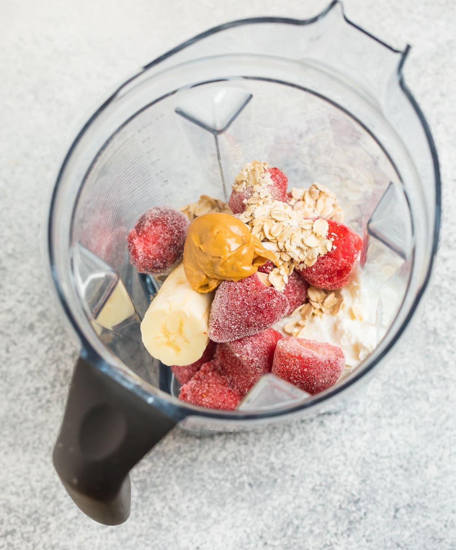 Strawberry banana Greek yogurt smoothie ingredients in a blender