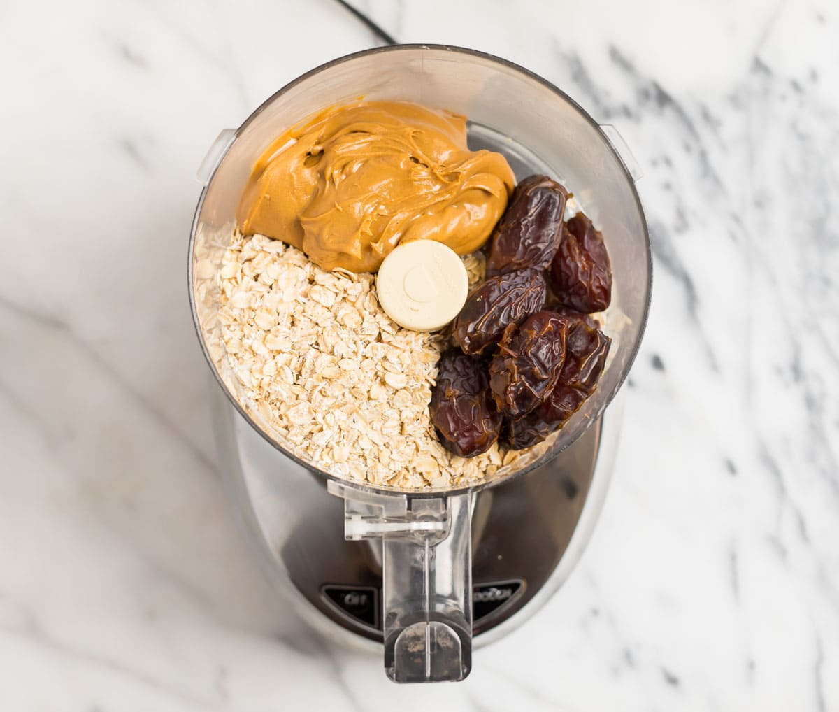 a food processor with dates, peanut butter, and oats