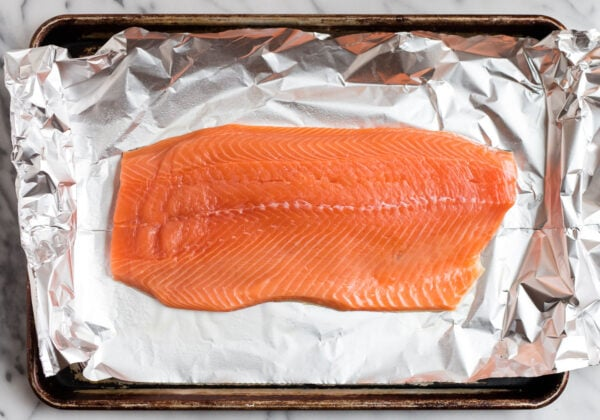 A healthy side of salmon on aluminum foil on a baking sheet