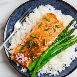 A fillet of healthy baked teriyaki salmon and asparagus on rice