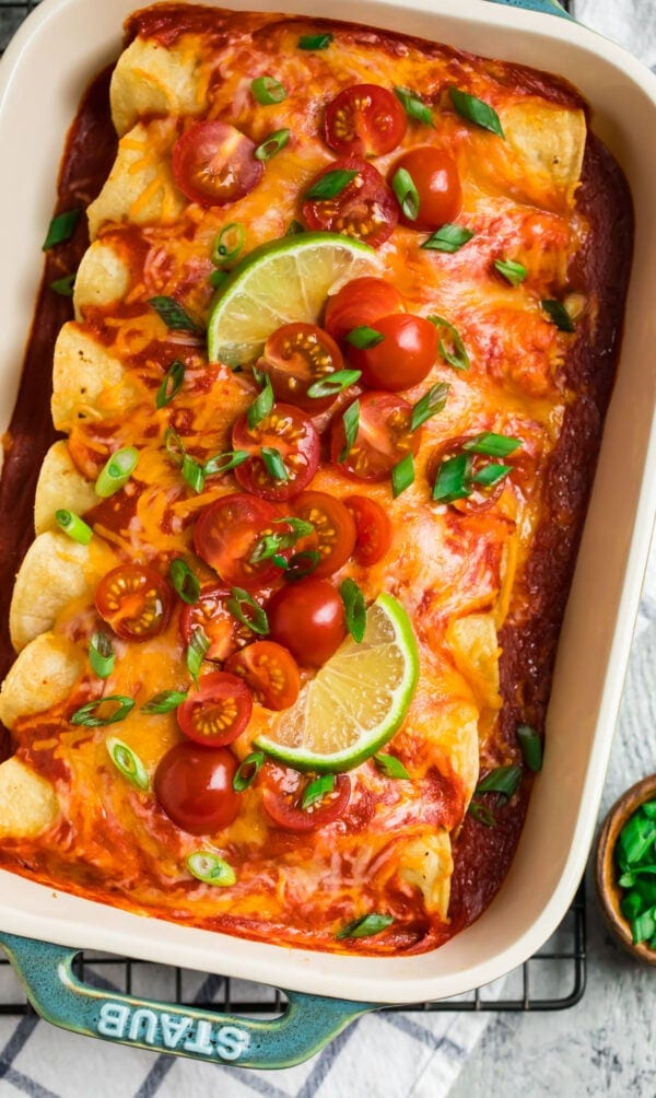 A blue casserole dish with creamy Instant Pot Chicken Enchiladas, topped with red enchilada sauce and cheese