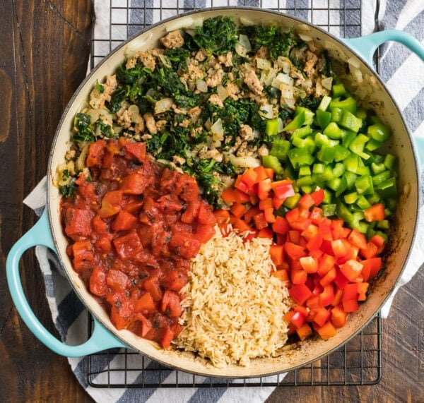 A Dutch oven with ground turkey, spinach, tomatoes, brown rice, and bell peppers