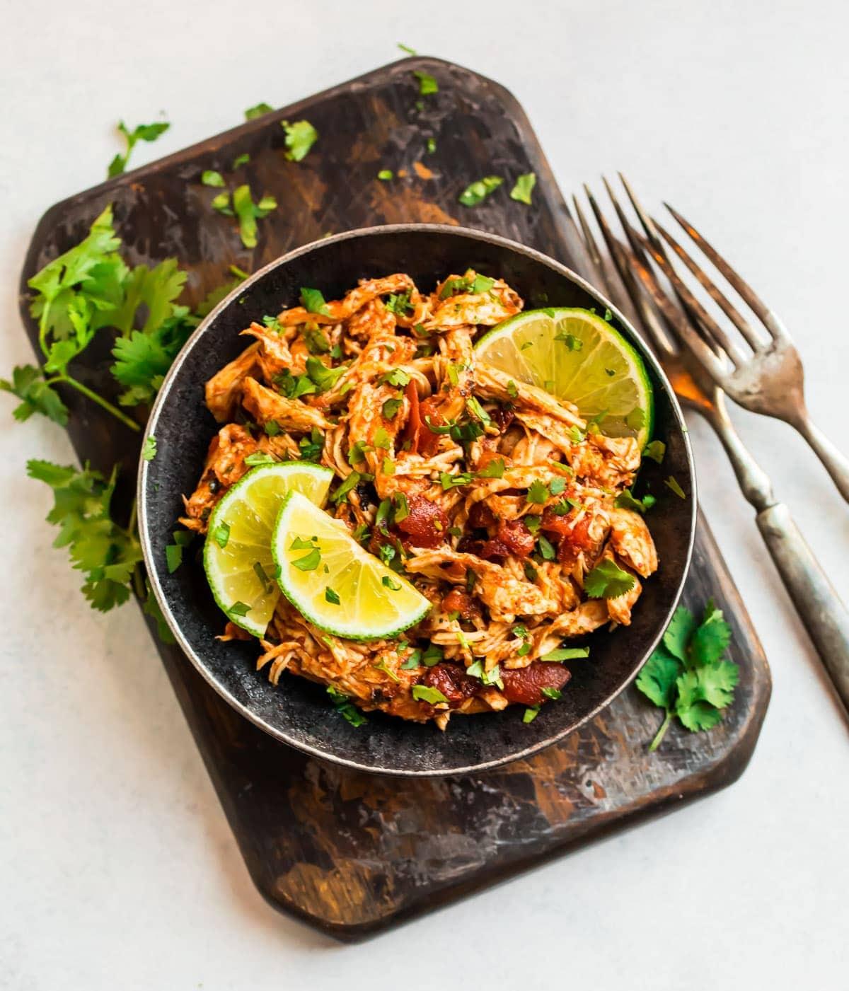 Un tazón lleno de pollo mexicano rallado hecho en la olla de cocción lenta.