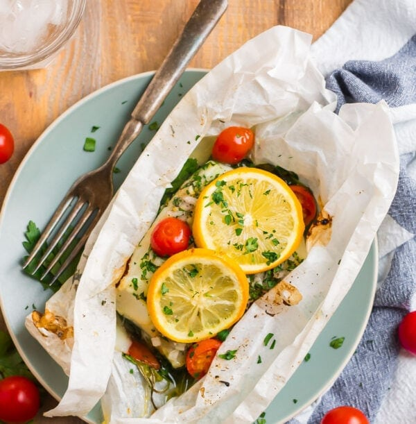 Fish baked inside a parchment paper pouch with vegetables and lemon