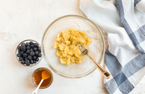 Mashed banana, blueberries, and honey for making healthy baked goods