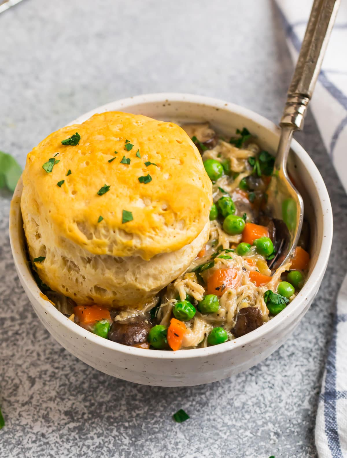 A bowl of healthy crock pot chicken pot pie with a biscuit