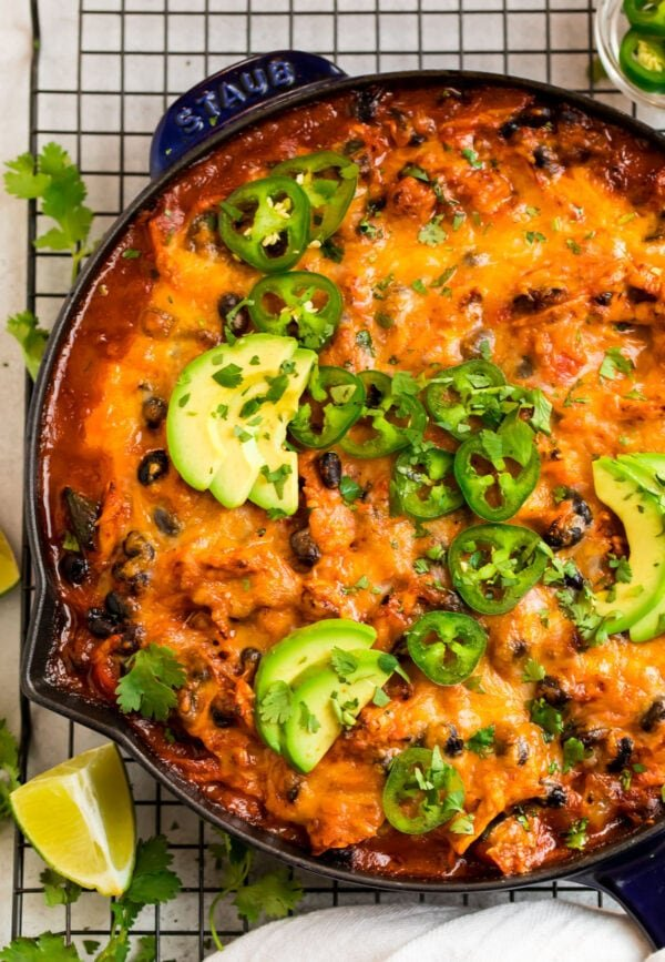 Chicken enchilada skillet in a large skillet with cheese and avocado