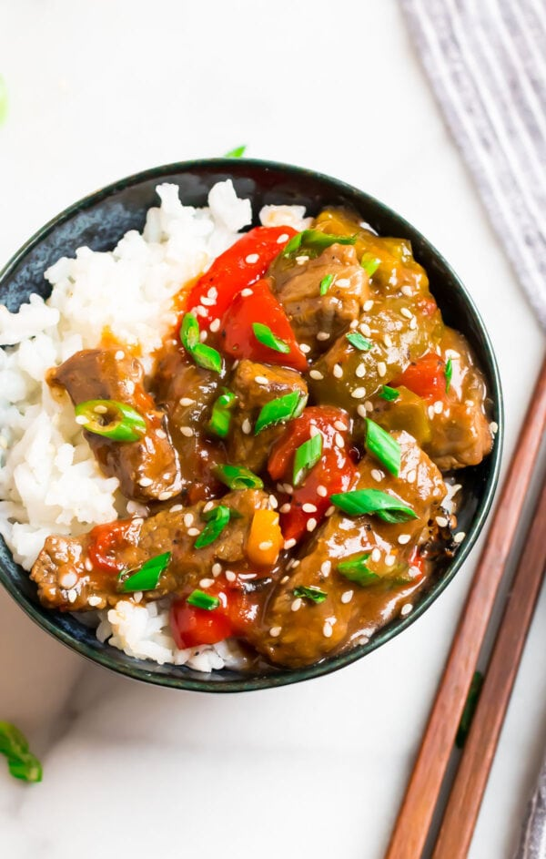 A bowl of crock pot pepper steak with peppers and white rice