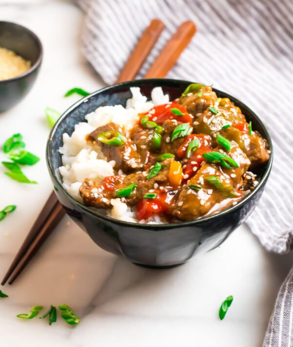 A bowl of crock pot pepper steak and rice with bell peppers