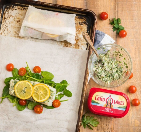 A piece of fish on parchment paper for baking with a lemon, butter, and herb topping