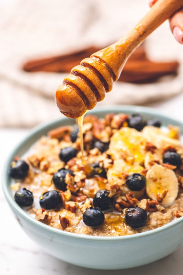 Honey dripping over a bowl of quick steel cut oats with fruit