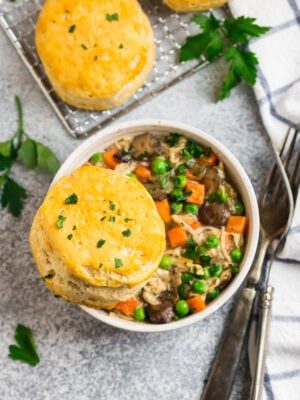 A bowl of crock pot chicken pot pie with biscuits