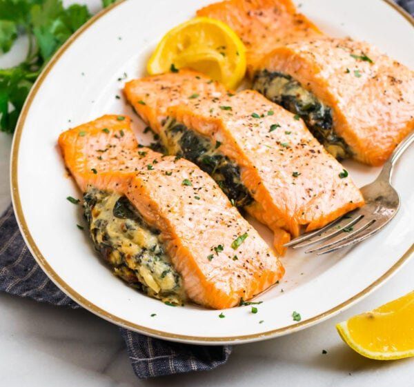 Spinach stuffed salmon fillets on a platter with lemon