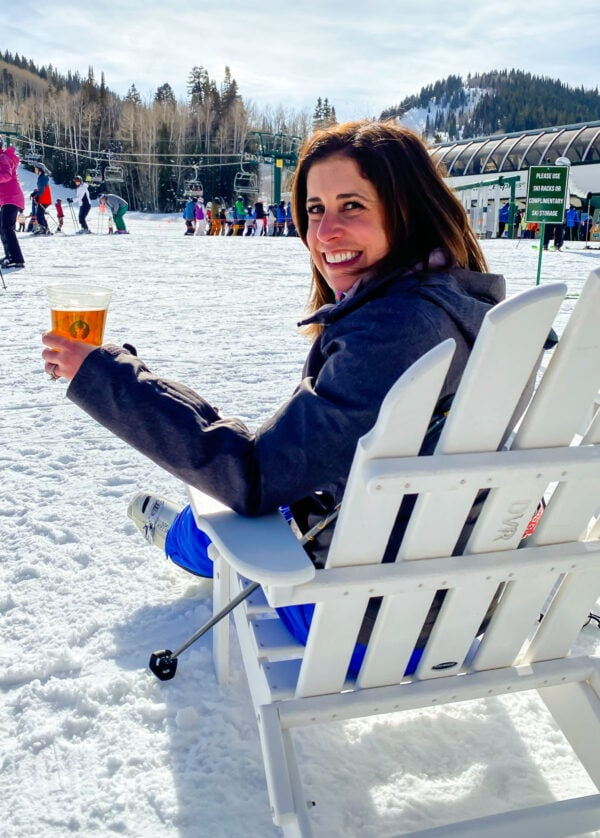A girl in ski clothes sitting in an Adirondack chair holding a beer