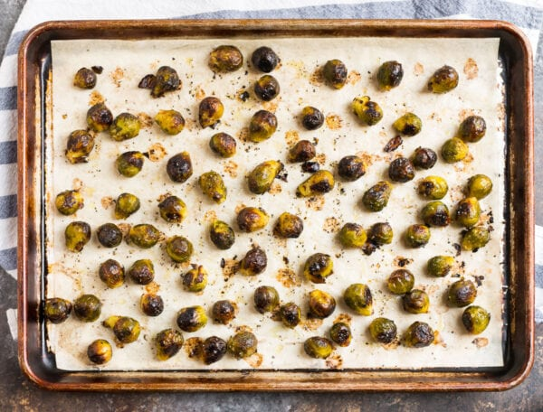 Roasted frozen Brussels sprouts on a parchment-lined baking sheet