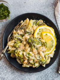 creamy cavatelli and broccoli pasta on a white plate with lemon