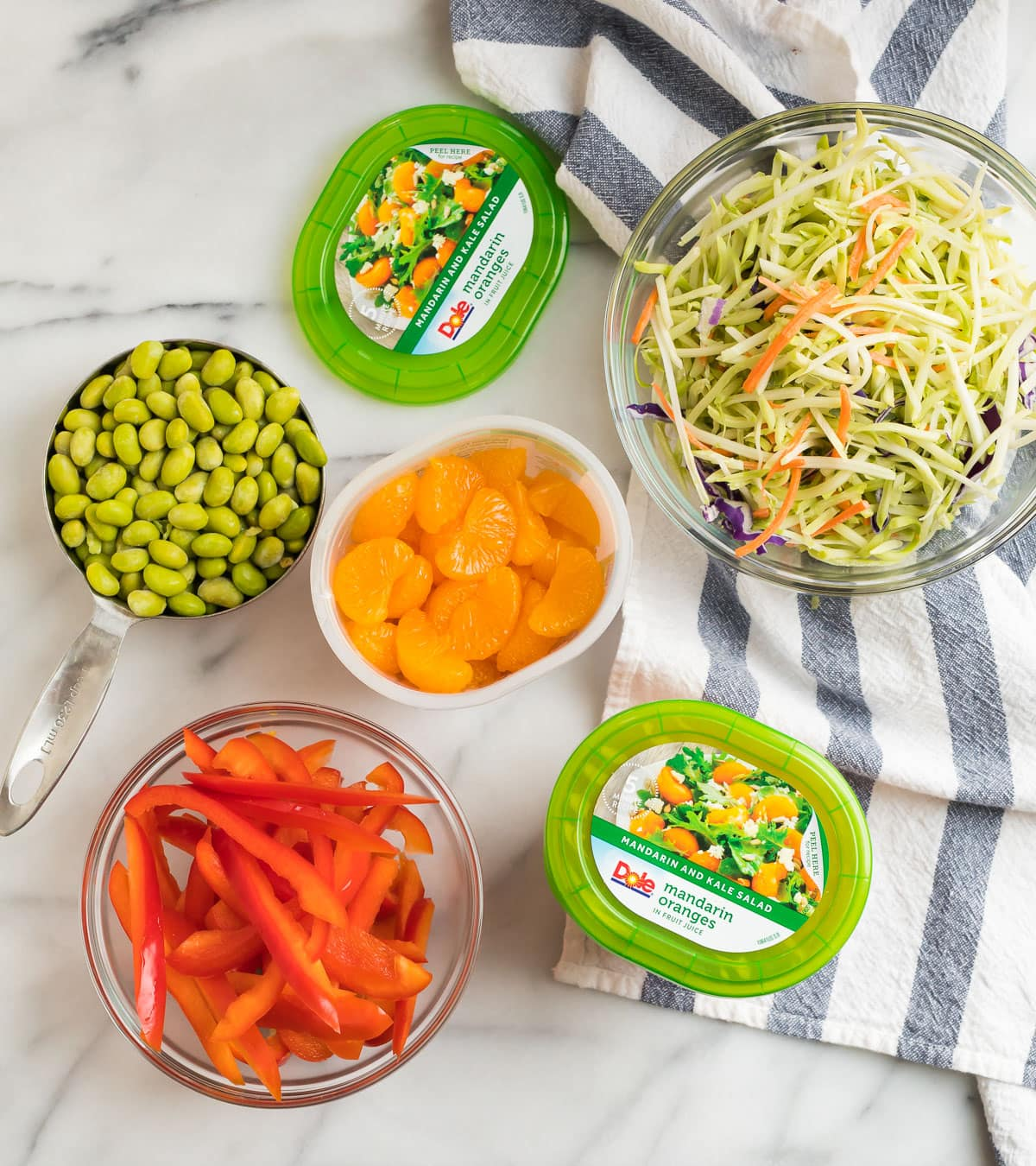 Ingredients for a healthy stir fry including edamame beans, red bell pepper, Mandarin oranges, and broccoli slaw