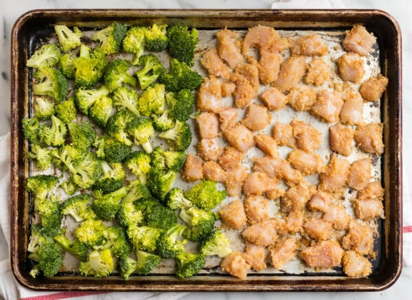 A sheet pan with broccoli florets and chicken pieces