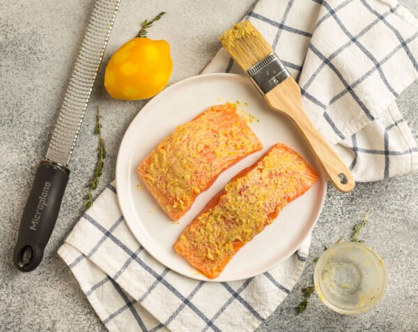 Two fish fillets on a white plate brushed with butter and mustard