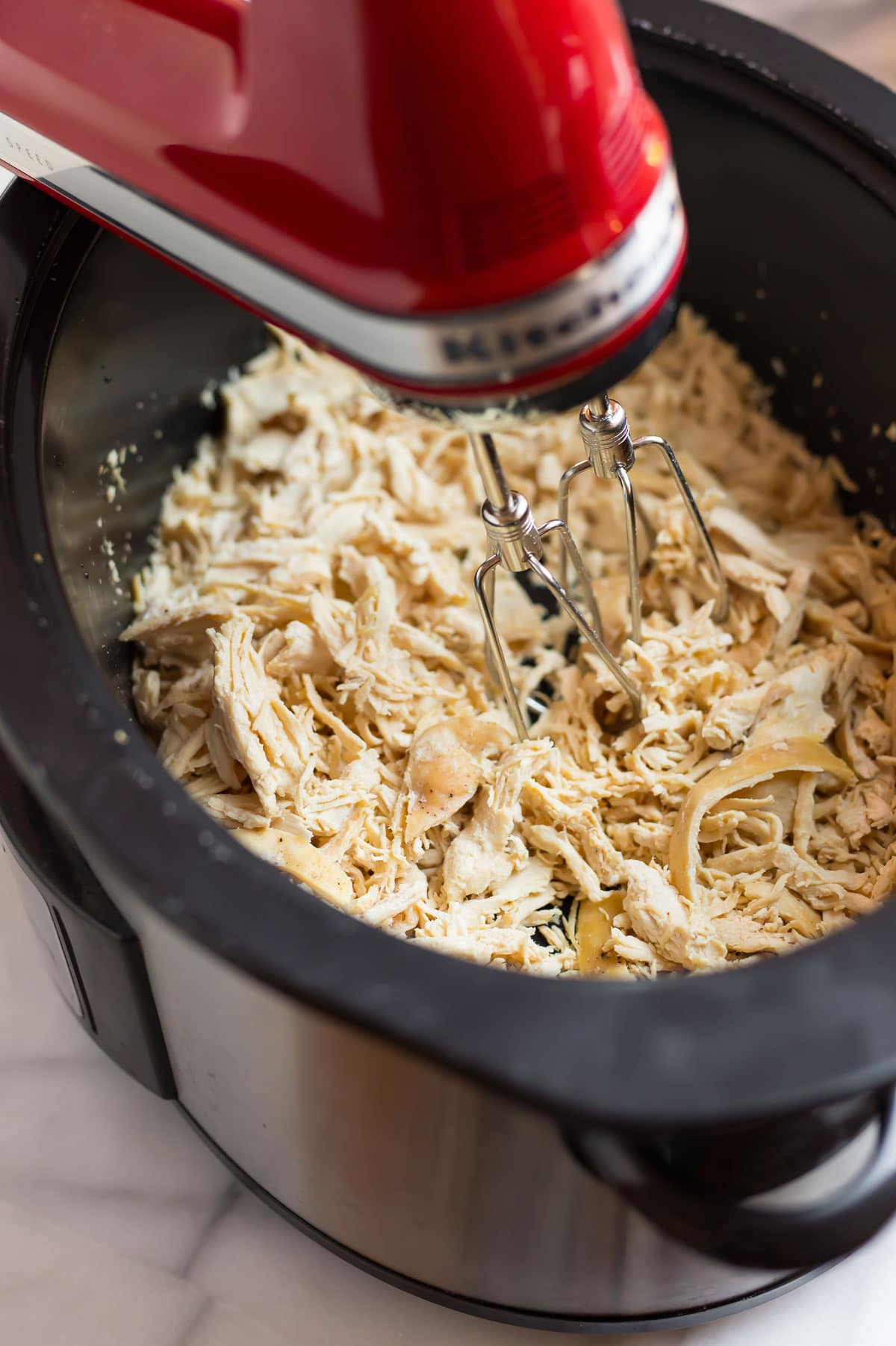 Chicken being shredded in a slow cooker with a hand mixer