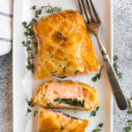 A white plate with salmon wellington, a dish of salmon on spinach, wrapped in puff pastry and baked