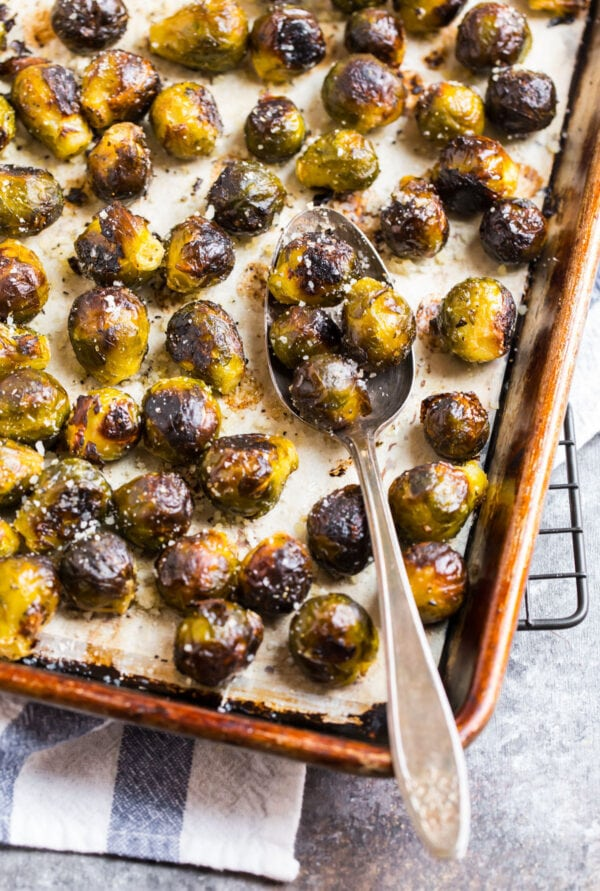 A spoon stirring a baking sheet full of roasted frozen Brussels sprouts
