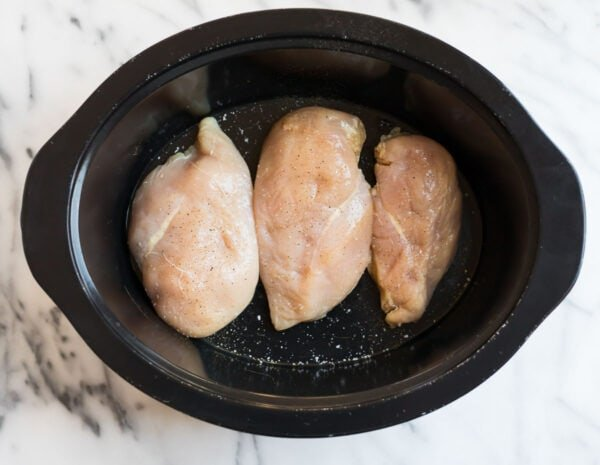 A slow cooker with three raw chicken breasts for making shredded chicken