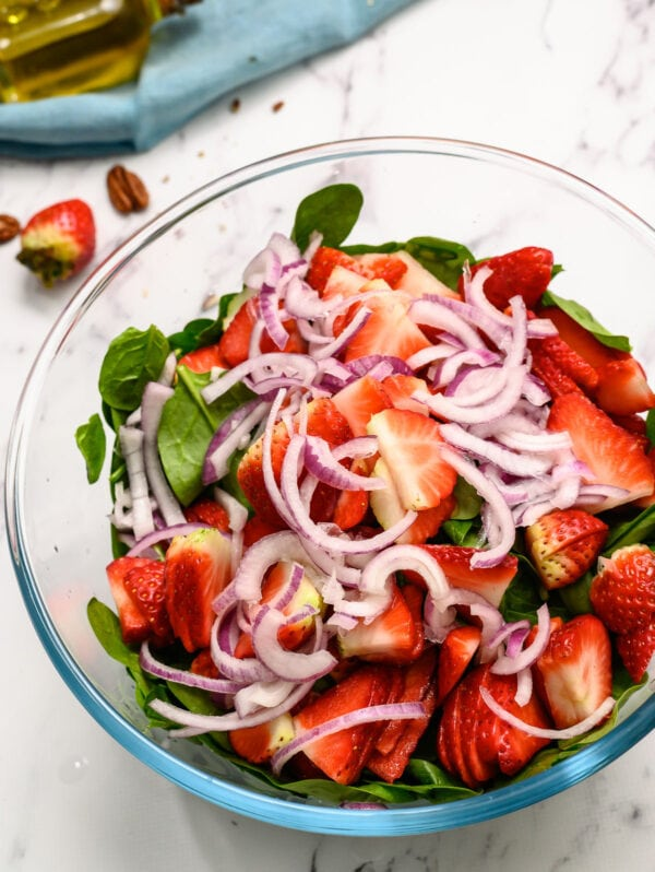 Strawberries, red onions, and spinach in a glass bowl