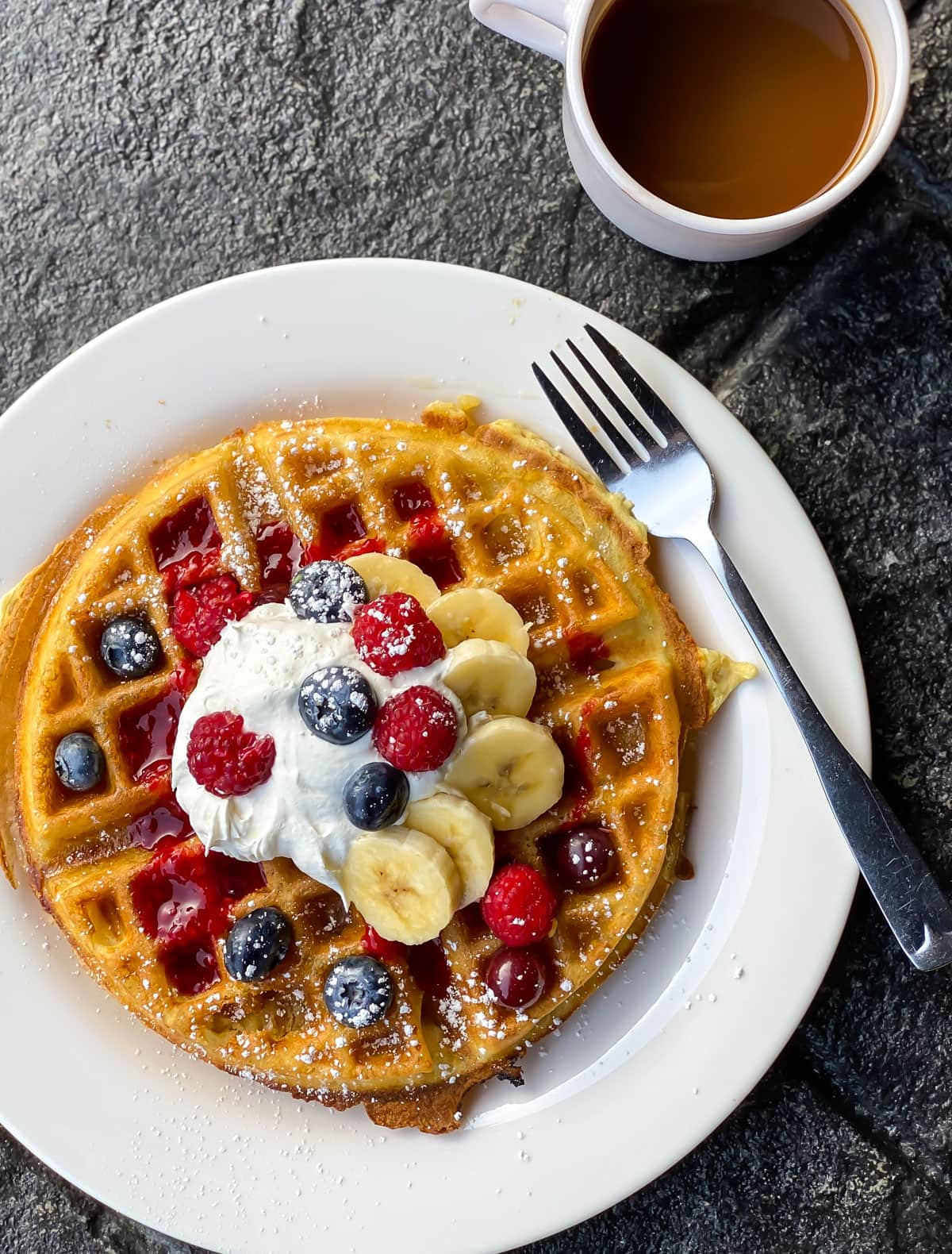 A waffle on a plate with fresh fruit and whipped cream