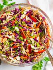 A fresh and healthy Asian Cabbage salad with raw cabbage, almonds, bell pepper and carrots in a ginger peanut dressing in a clear salad bowl