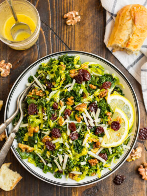Kale and Brussel Sprout Salad with Maple Vinaigrette in a white salad bowl topped with walnuts