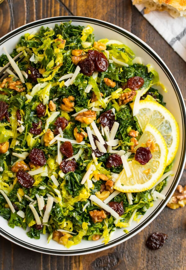 A white salad bowl with kale and brussels sprouts salad topped with Parmesan cheese