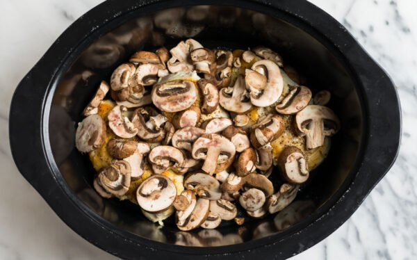 Mushrooms on top of chicken breasts in a slow cooker