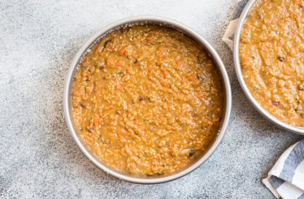 Two cake pans filled with batter for gluten free carrot cake