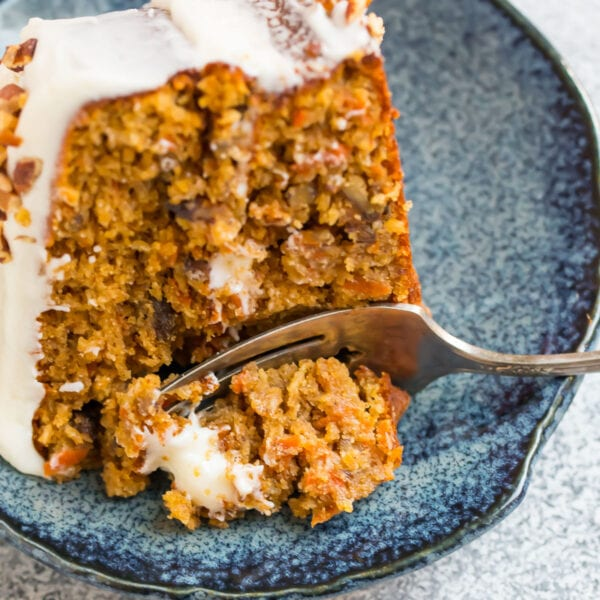A slice of fluffy gluten free carrot cake with cream cheese frosting on a blue plate